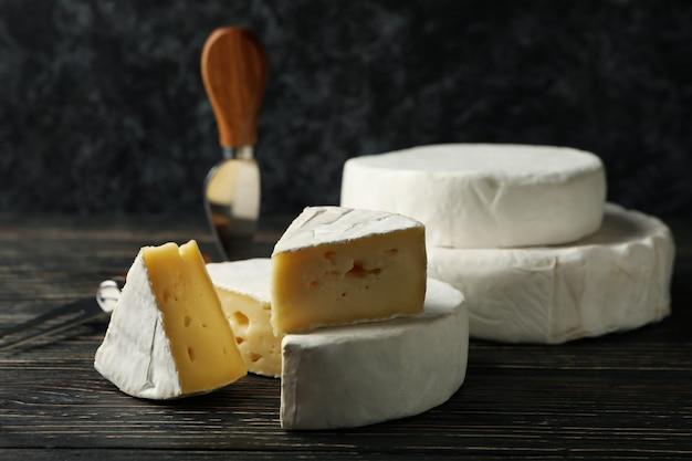 木製の背景にカマンベールチーズとナイフ、クローズアップ