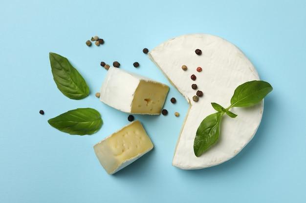 Сыр камамбер, базилик и перец на синем фоне