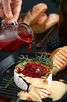 Camembert cheese in cast-iron pan, oven baked with figs, walnuts and rosemary