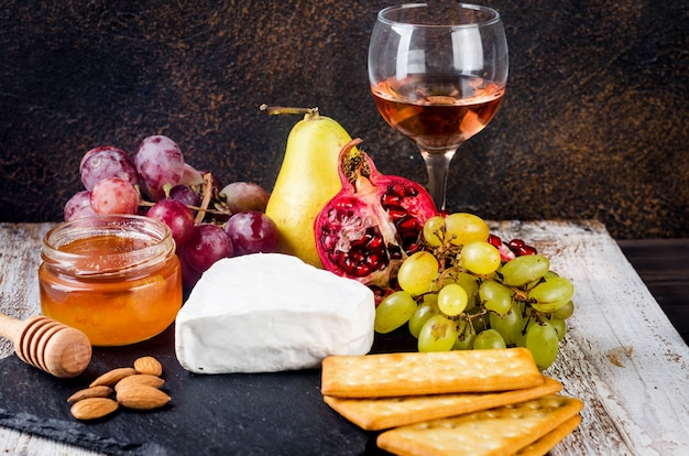 蜂蜜、ナッツ、つるのカマンベールチーズのクローズアップ。絶妙なチーズプレート、ワインフード。カマンベール、そよ風。やわらかいフレンチチーズ。イタリア料理。乳製品。
