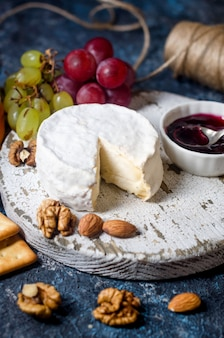 Camembert cheese close-up with honey, nuts, vine. exquisite cheese plate, wine food.