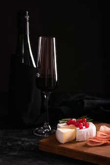 Camembert cheese decorated with red currant on a wooden board and red wine