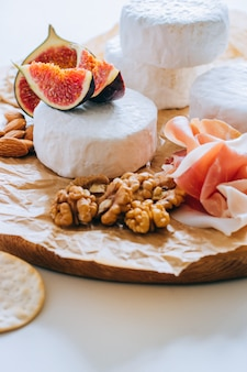 Camembert cheese, figs, jamon, honey and grapes. cheese plate on marble background