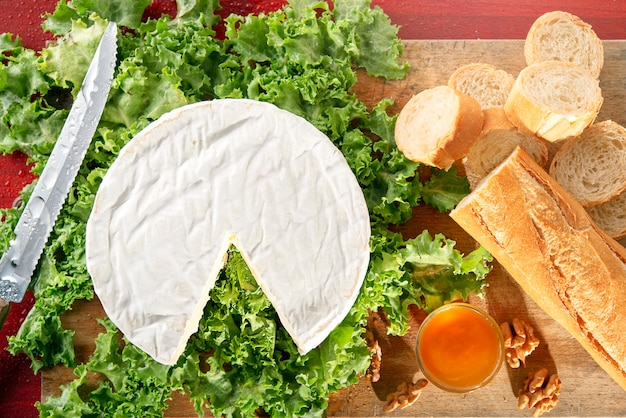 Camembert cheese on green salade with honey bowl and bread baguette