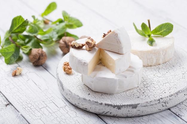 Сыр камамбер на деревянной доске с орехами и мятой. итальянская, французская кухня