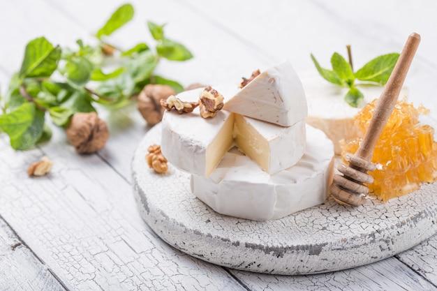 Сыр камамбер на деревянной доске с орехами, медом и мятой. итальянская, французская кухня