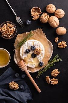 Сыр камамбер на бумаге черника орехи медовый бутерброд на сером фоне итальянский французский