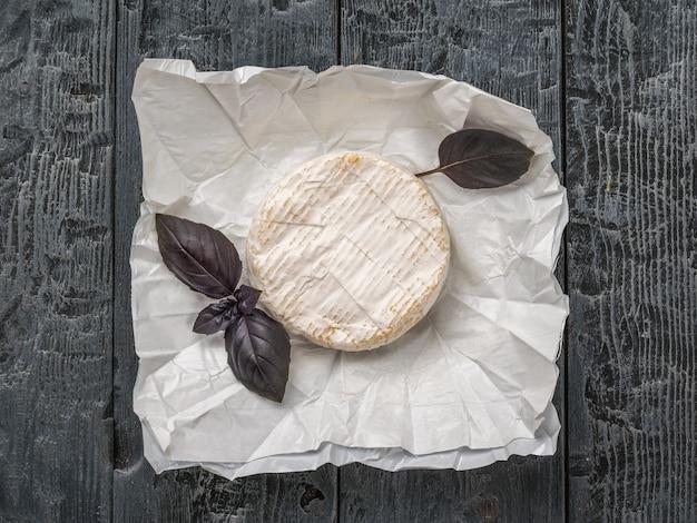 Сыр камамбер на бумаге с веточкой базилика на черном деревянном столе. продукт из натурального молока.