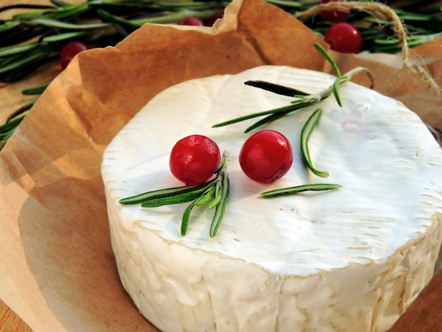 Camembert cheese in paper, cranberry and fresh rosemary.
