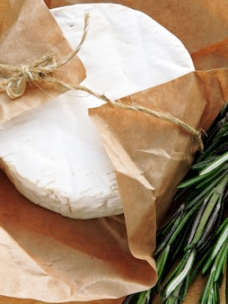 Camembert cheese in paper and fresh rosemary.