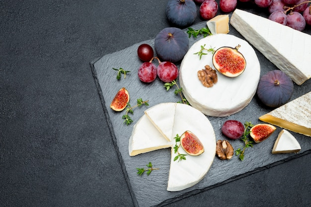 Camembert cheese and a slice cut on stone serving board