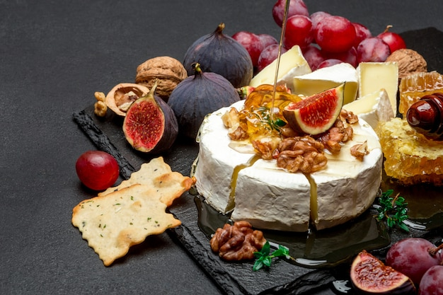 Camembert cheese and walnuts on stone serving board