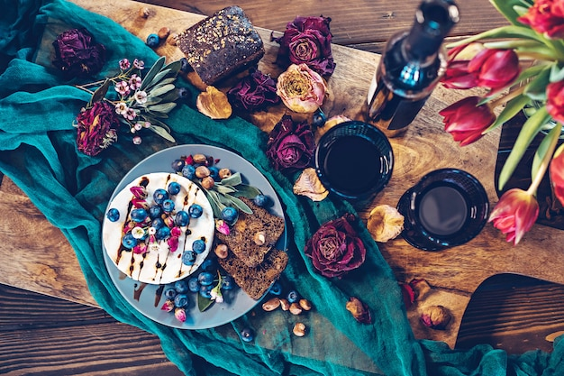 Camembert cheese with blueberries, bread, nuts and red wine decorated with flowers