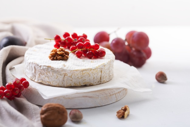 Camembert cheese with fruits, nuts and berries, selective focus