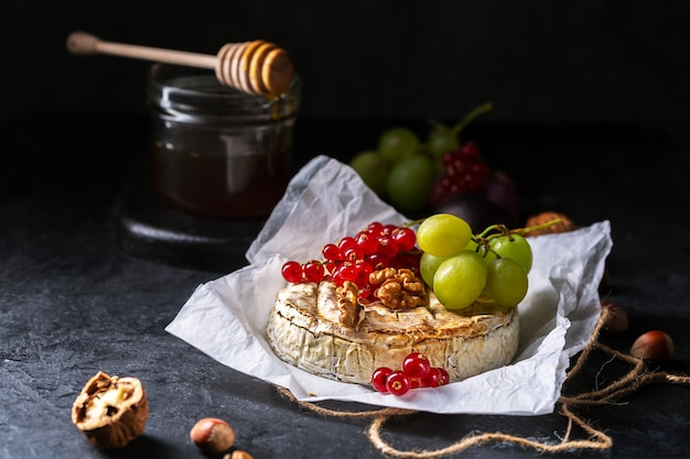 Camembert cheese with fruits, nuts and berries