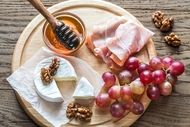 Camembert cheese with nuts and prosciutto