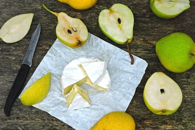 Сыр камамбер с грушами на деревянной поверхности.