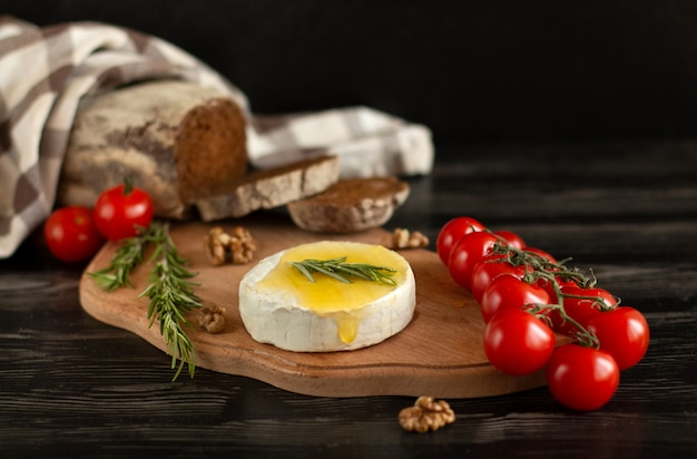 Camembert cheese  with rye bread, nuts, honey, cherry tomatoes and rosemary on a wooden board