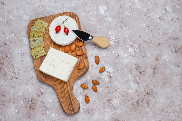 Camembert cheese with two glass red wine and cheese knife on board on brown concrete surface