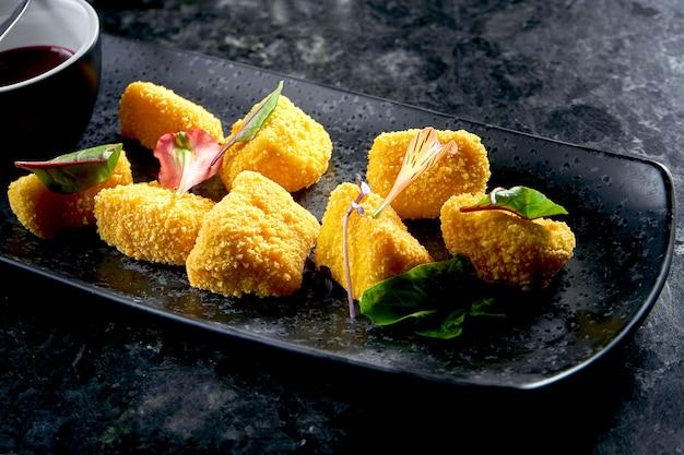 잼을 곁들인 카망베르 튀김은 어두운 테이블에 검은 접시에 담겨 있습니다. 레스토랑 스낵. 푸드 펍