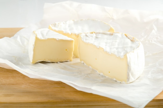 Camembert with piece on white wrapping paper