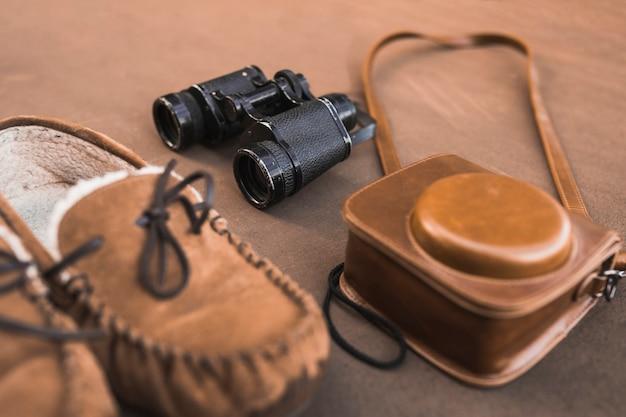 Камера и бинокль возле обуви