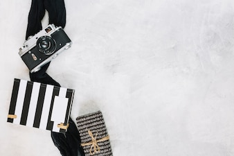 Camera and cloth near notebook and gift