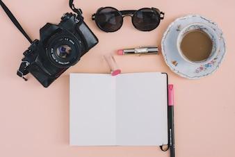 ノートパソコンやアクセサリーに近いカメラとコーヒー