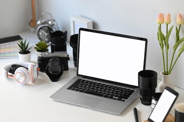 白いテーブルの上のカメラとラップトップ