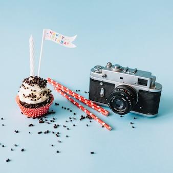 Camera and straws near birthday muffin