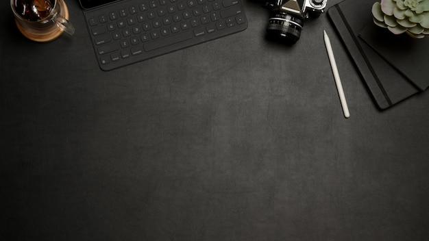 黒いテーブルの上のカメラとタブレットのキーボード