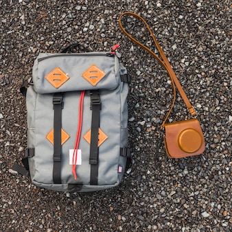 Camera and backpack on gravel