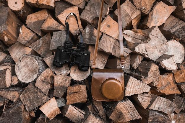 Camera and binoculars on firewood