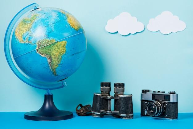 Camera and binoculars near globe and clouds