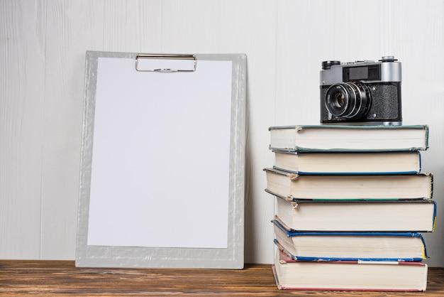 Macchina fotografica e libri vicino alla lavagna per appunti