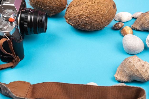 Camera,coconuts and shells on a blue background.background for the traveler