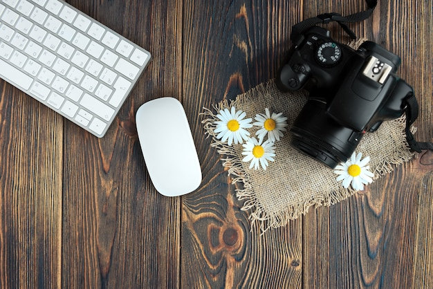 Camera, computer keyboard and field flowers on dark wood.