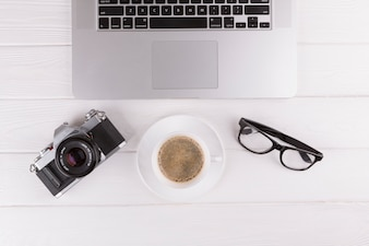 Camera, eyeglasses, cup and laptop