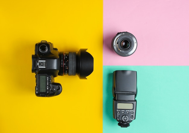 Camera, flash, lens on a pastel surface.