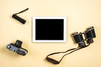 Camera; flashlight; binocular and digital tablet on beige background