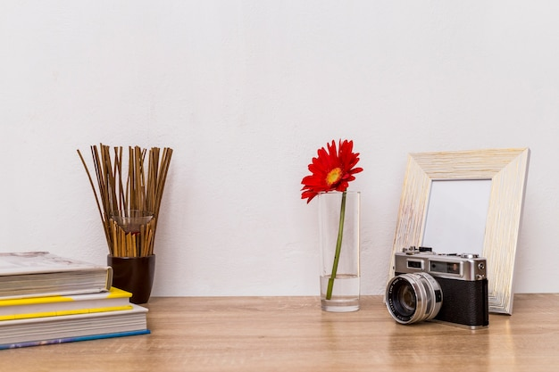 Camera flower photo frame and books on table