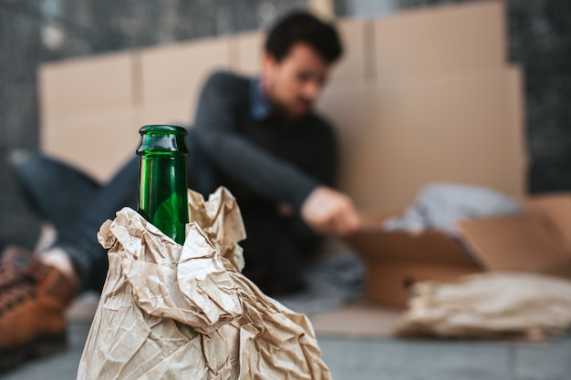 Camera is concentrated on green bottle standing in front of guy who's sitting on the cardboard and reaching the box. body of bottle is covered with paper.