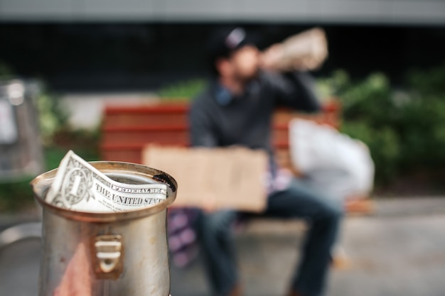 Camera is focused on metal cup. there is a dollar bill in it. guy is sitting on the bench and drinking from bottle. it is his cup.