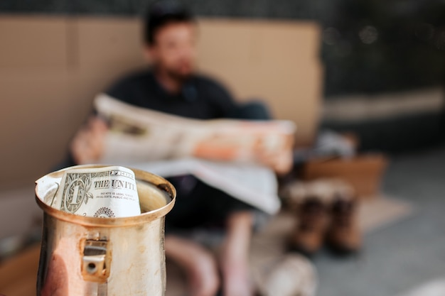 Camera is focused on metal cup with dollar in it. it is beggar's cup. homeless man is sitting on cardboard and reading newspaper. he is relaxing.