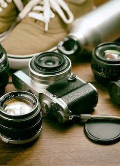 カメラ、レンズ、双眼、キャンバスシューズ、レトロな木製テーブルのスポーツボトル