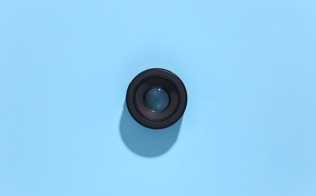 Camera lens on blue bright background with deep shadow.