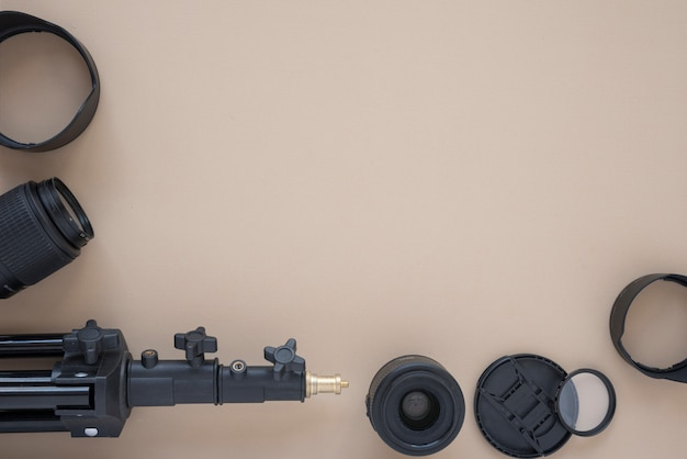 Camera lens and camera accessories arranged on colored background
