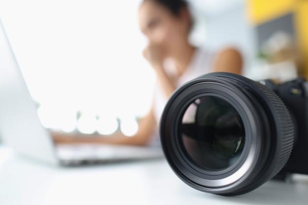 Объектив камеры на фоне женщины, работающей за компьютером, работая фотографом и журналистом