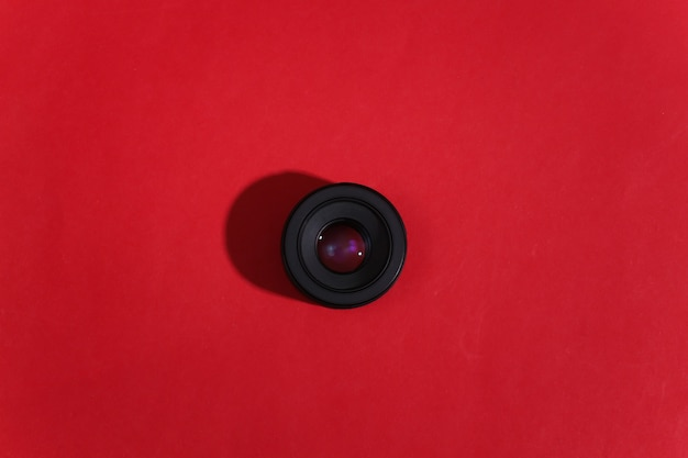 Camera lens on red bright background with deep shadow.
