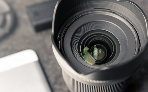 Camera lens with camera accessories lay on the photographer work space